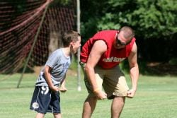 A counselor demonstrating a soccer technique to a young camper.
