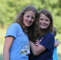 Two young female campers embracing and smiling.