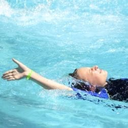 A young female camper doing the backstroke in the Camp Olympia pool.