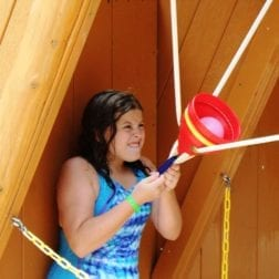 A young female camper shooting a water balloon from a battle station.