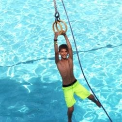 A young male camper hanging on the trolley during free swim.