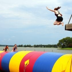 A female camper jumping from a platform onto an inflatable blob anchored on the lake.