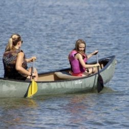 Two female campers canoeing on Lake Livingston.