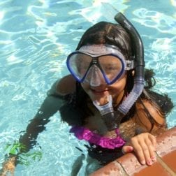 A young female camper snorkeling in the Camp Olympia pool.