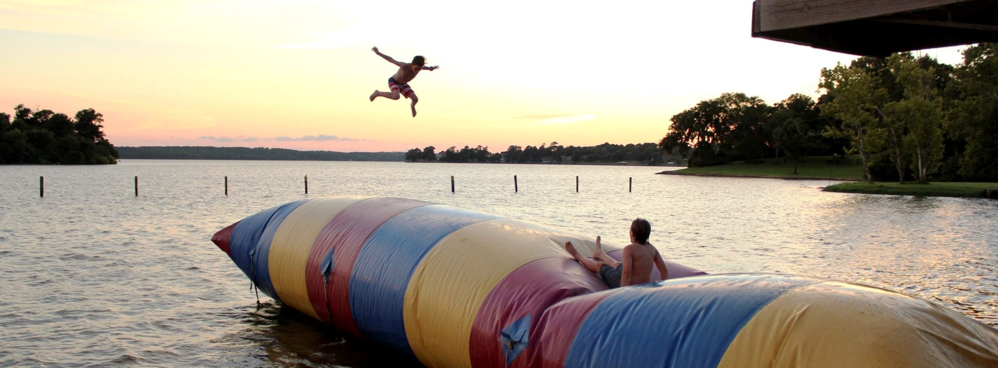 Two young boys jumping on a floating inflatable blob on a lake.