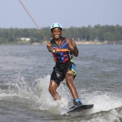 A young male camper wakeboarding on Lake Livingston.