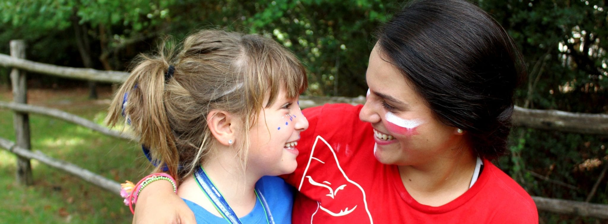 Close-up of a camp counselor sharing a smile with a camper.