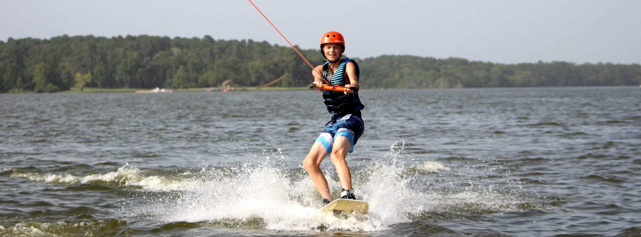 A young man riding a wakeboard on a lake.
