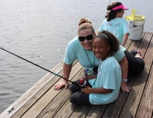 Girl camper fishing on a dock