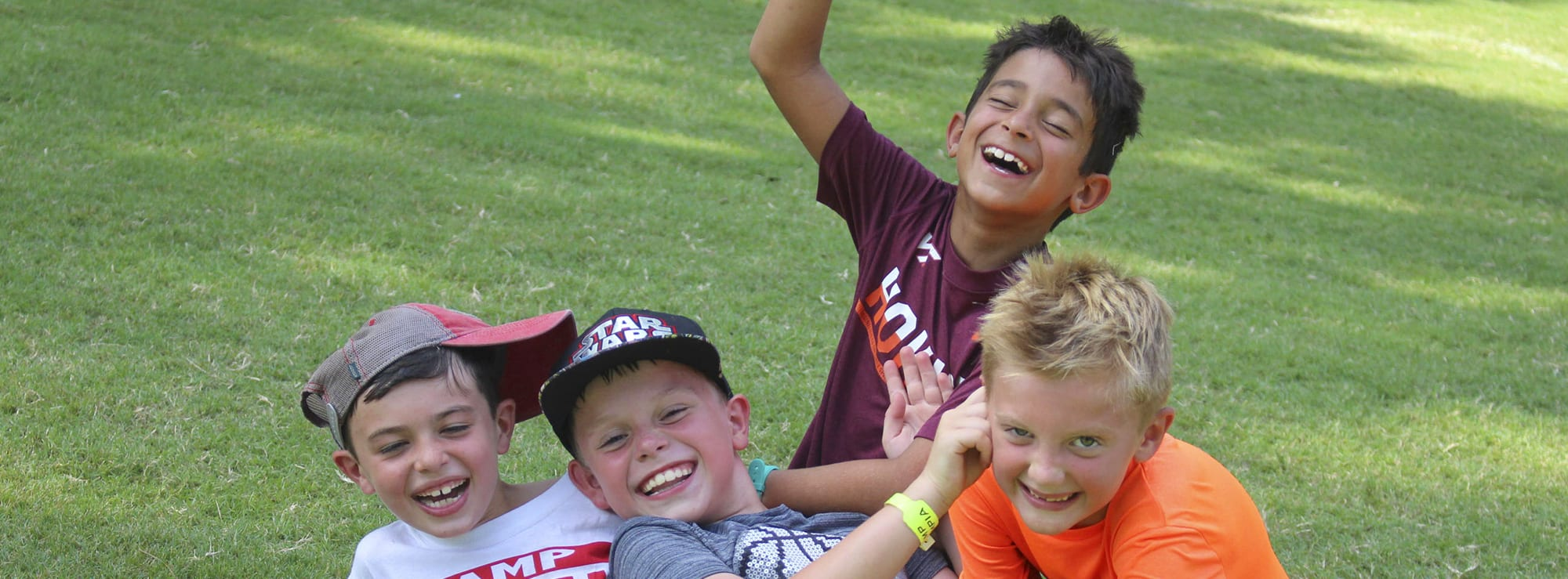 Close-up of four campers smiling and laughing while playing outdoors.
