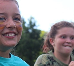 two girls running outdoors at camp